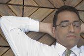 Hispanic businessman with hands behind head