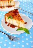 Cheese cake in plates on tablecloth closeup