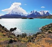 Magic beauty of the lake of Pehoe. The strong wind drives turquoise waves on the lake, grandiose rocks Los Kuernos are covered with snow and ice