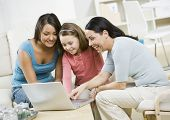 Hispanic mother and daughters looking at laptop