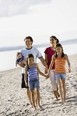 Multi-ethnic family walking on beach