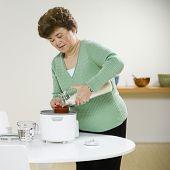 Senior Asian woman making rice