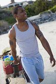 African man pulling wagon on beach