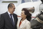 Asian businesspeople laughing next to airplane