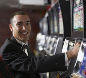 Hispanic man at slot machine
