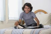 Mixed Race boy reading on bed