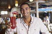 Hispanic man holding cocktail
