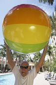 Senior man holding beach ball over head