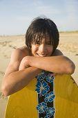 Asian boy leaning on surfboard