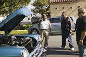 Tattooed Hispanic men looking at car