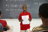 African American boy holding paper in front of class