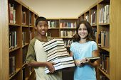 Multi-ethnic students holding library books