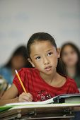 pic of pre-adolescent girl  - Asian girl at desk in classroom - JPG