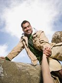 foto of pacific islander ethnicity  - Pacific Islander man helping person climb - JPG