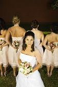 Hispanic bride in front of bridesmaids