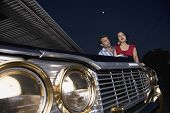 Multi-ethnic couple leaning on show car