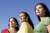 Row of multi-ethnic women under blue sky