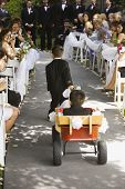 Hispanic boy pulling brother down aisle at wedding