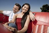 Multi-ethnic couple in backseat of convertible
