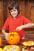 Boy carving his jack-o-lantern for Halloween - removing the seeds
