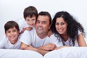 Happy family with kids on a lazy day - portrait in bed