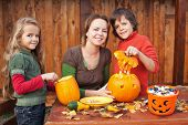 Kids carving jack-o-lanterns for Halloween - with a little help from their mother