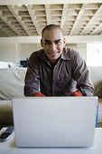 African American man sitting behind laptop