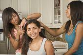 Hispanic teenaged girls fixing friend's hair
