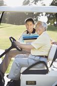 Asian father and adult son in golf cart