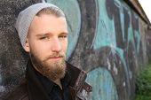 Portrait of stylish guy with beard in street
