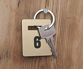 Hotel suite key with room number 6 on wood table