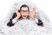 Terrified man covered in a pile of shredder paper isolated on white background