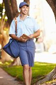 Mailman Walking Along Street Delivering Letters