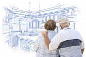 Curious Senior Couple Looking Over Blue Custom Kitchen Design Drawing.