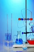 Fixed laboratory glassware on support on colorful background