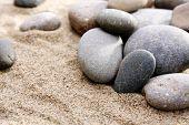 Gray sea pebbles on sand background