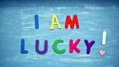 I Am Lucky Written On A Blue Wood Background