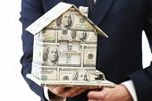 Model of house made of money in male hand isolated on white background
