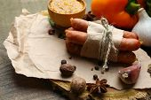 Composition of thin sausages, mustard in bowl and spices on wooden background