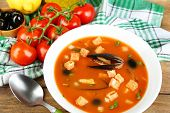Tasty soup with mussels, tomatoes and black olives in bowl on wooden background