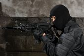 stock photo of extremist  - Terrorist in black uniform targeting with M - JPG