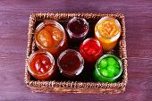 Homemade jars of fruits jam in wicker basket and color wooden background