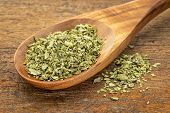 organic dried oregano leaf on a wooden spoon against a grunge wood background