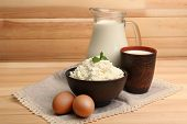 Cottage cheese in clay bowl with jug of milk and eggs on wooden planks background