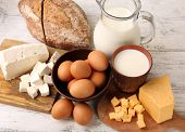 Tasty dairy products with bread on wooden table close up