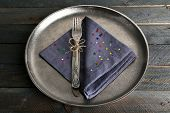 Silverware tied with rope on napkin and metal tray and wooden planks background