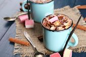 Mugs of hot coffee with marshmallow on burlap cloth with cinnamon and vanilla sticks on color wooden table background