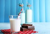 Glass and bottles of milk with chocolate chunks on dots napkin and color wooden planks background