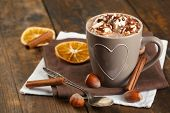 Cup of hot coffee with marshmallow on napkins with hazelnut, cinnamon and dried orange on rustic wooden planks background