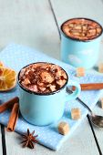 Mugs of hot coffee with marshmallow on napkin with lump sugar, cinnamon, star anise and dried orange on color wooden table background